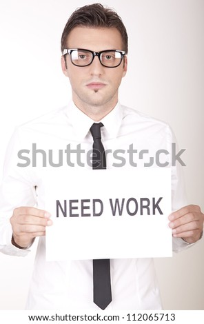 Portrait of a young attractive man holding a sign need work.