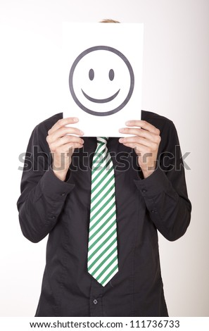 Portrait of a young attractive man holding a smiley face.