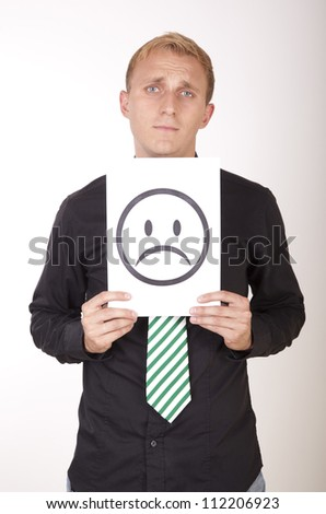 Portrait of a young attractive man holding sad smiley face.