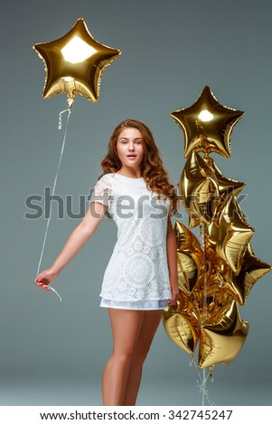 Portrait of a young attractive woman in a white dress, holding bunch of many gold balloons, over light  background