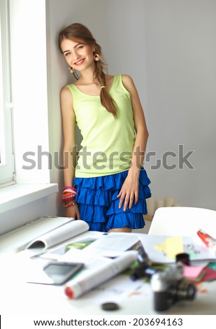 Portrait of a young beautiful photographer woman on the table.