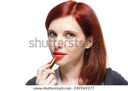 Portrait of a young beautiful woman applying  lipstick for lips on a white background.