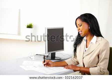 Portrait of a young business female smiling and working on documents
