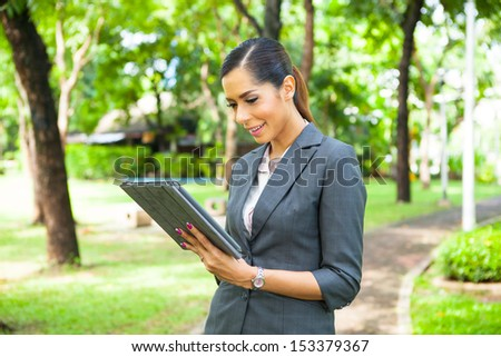 Portrait of a young businesswoman working with tablet at the park.