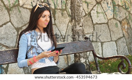 Portrait of a young Caucasian brunette woman with long hair while using mobile device in park.