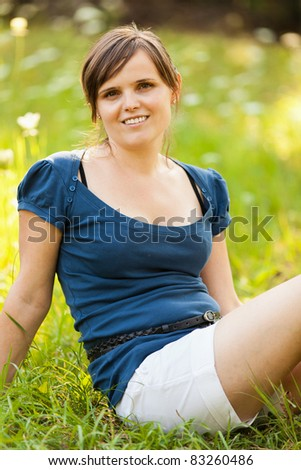 Portrait of a young caucasian woman relaxing outdoor in a meadow