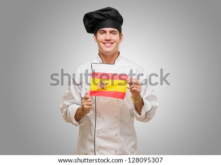 Portrait Of A Young Chef Holding Spanish Flag against a grey background