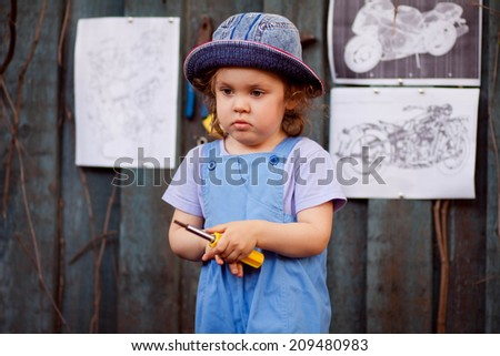 Portrait of a young child in the image of the master, the master's assistant in the studio, working with tools