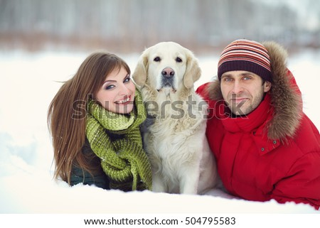 portrait of a young couple with a dog on a winter walk. man and woman with labrador outdoors