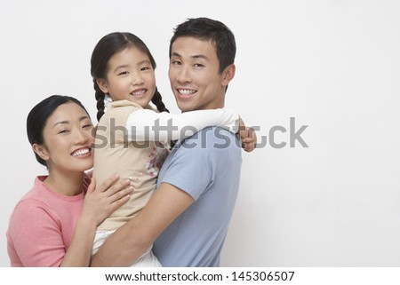 Portrait of a young couple with daughter against white background