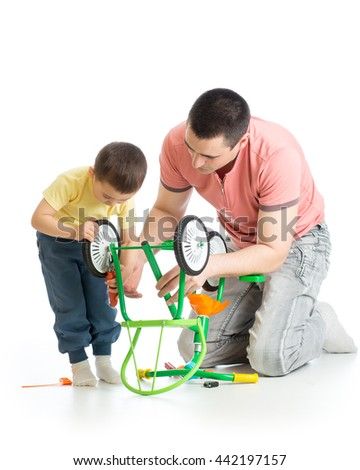 Portrait of a young father and his son kid repair a broken bicycle together at home