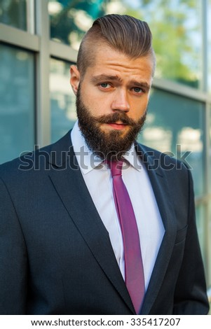 Portrait of a young focused businessman outside the office building