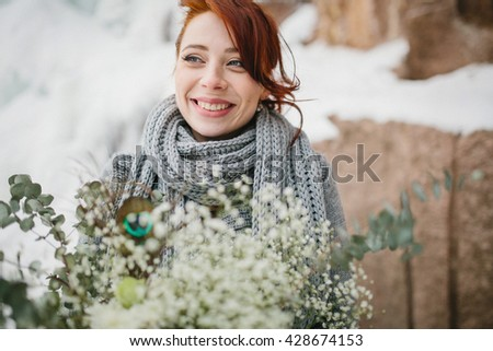 Portrait of a young girl bride with a bouquet. Against the background of a winter landscape with snow