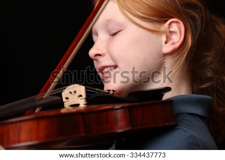 Portrait of a young girl playing violin on black background
