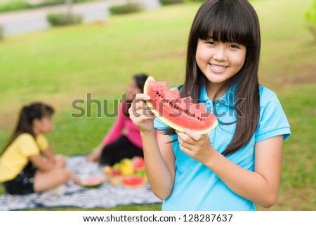 Portrait of a young girl standing with watermelon in hands