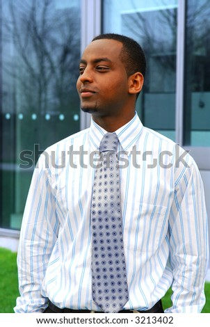Portrait of a young handsome businessman next to a corporate building