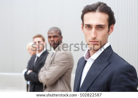 portrait of a young handsome businessman with other businessmen in background