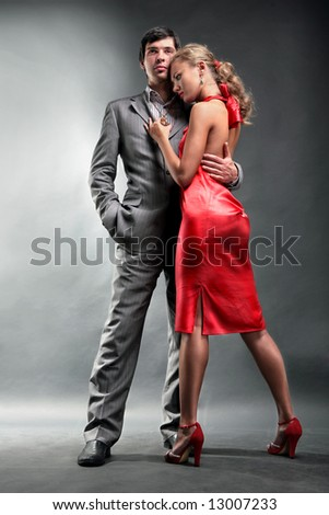 Portrait of a young handsome couple. Young woman embraces man. Woman in a red dress