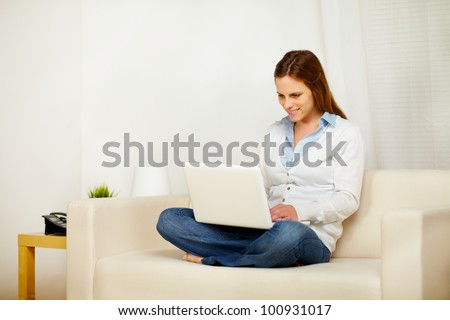 Portrait of a young lovely woman working on sofa with a laptop