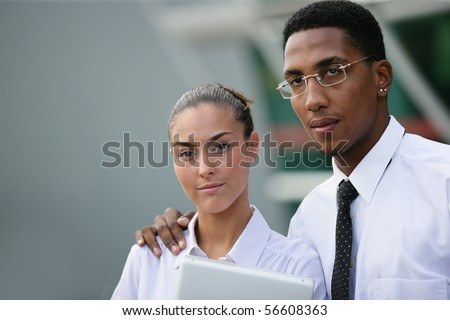 Portrait of a young man in suit near a young woman in suit holding a laptop computer