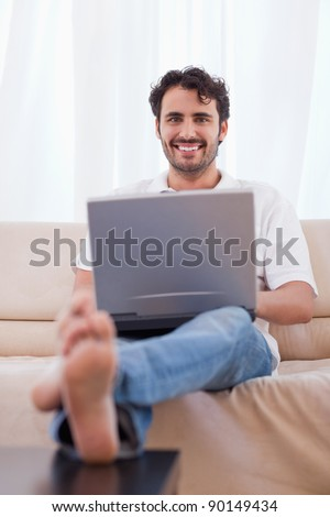 Portrait of a young man using a notebook in his living room
