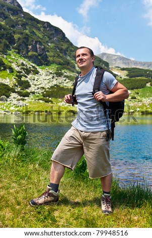 Portrait of a young mountaineer man with a backpack hiking into the mountains