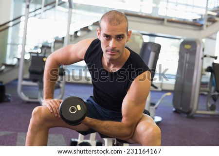 Portrait of a young muscular man exercising with dumbbell in the gym