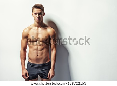 Portrait of a young sexy muscular man in underwear against white wall with copy space