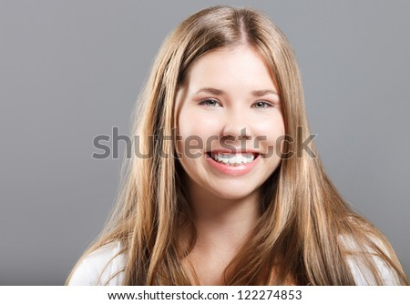 Portrait of a young smiling girl over gray background