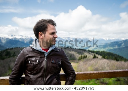 Portrait of a young smiling wanderer man traveler enjoying his recreation time in nature