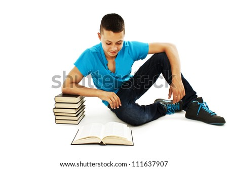 Portrait of a young student reading a book on the floor.  Isolated on white background