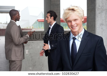 portrait of a young teenage boy in a suit with other businessmen in the background
