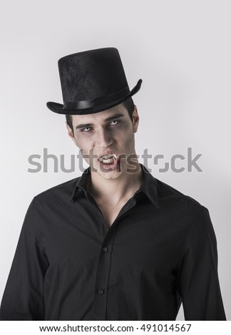 Portrait of a Young Vampire Man with High Hat and Black T-Shirt, Looking at the Camera, On Light Background.