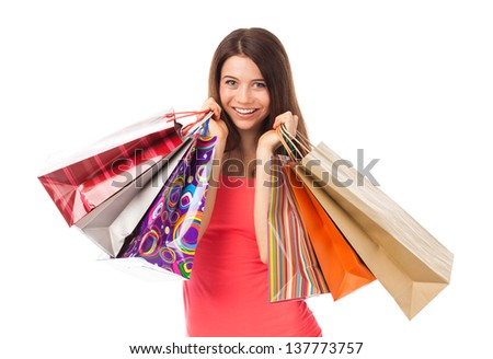 Portrait of a young woman holding shopping bags and smiling, isolated on white