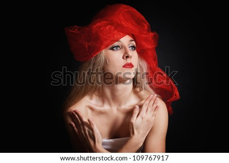 Portrait of a young woman in a red headdress on a black background