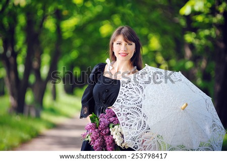 portrait of a young woman in a spring park with an umbrella.