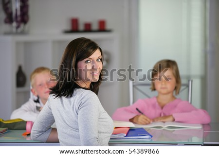 Portrait of a young woman in front of children doing homework