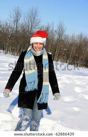 Portrait of a young woman in the snowy forest with santa hat