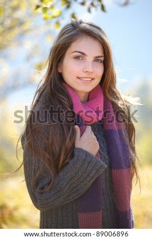 Portrait of a young woman on a chilly sunny day of autumn outdoor.