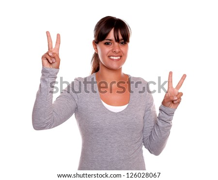 Portrait of a young woman smiling and showing you victory sign on gray t-shirt against white background