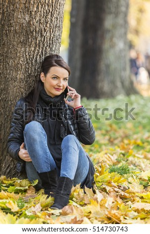 Portrait of a young woman with a mobile sitting in a yellow autumn forest.
