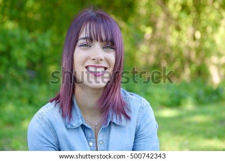 portrait of a young woman with green eyes and red hairs, outdoors