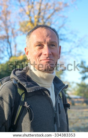Portrait of active man with backpack relaxing in a autumn park, standing on the background of the blue autumn sky, enjoying life and smiling. Pure clear air.