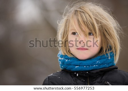 Portrait of adorable little kid boy with long blond hair outdoors. Child with blue scarf walking on a windy day