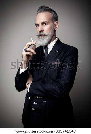 Portrait of adult businessman wearing trendy suit and holding cigarette against the empty wall. Vertical