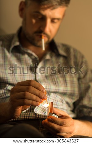 Portrait of adult man addicted to cigarette