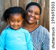 Portrait of African mom and daughter against wooden fence. - stock photo