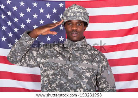 Portrait Of Afro-american Army Soldier Saluting In Front Of American Flag