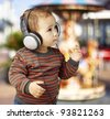 portrait of an adorable kid with headphones listening to music against a carousel background - stock photo