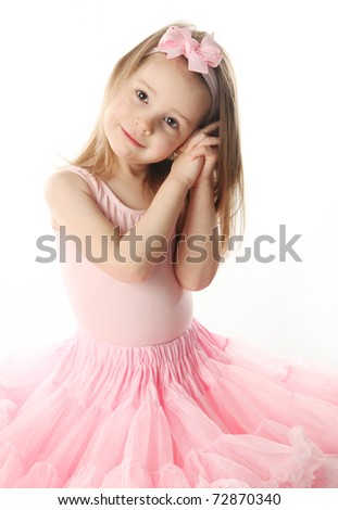 Portrait of an adorable preschool age girl playing dress up wearing a ballet tutu, isolated on white